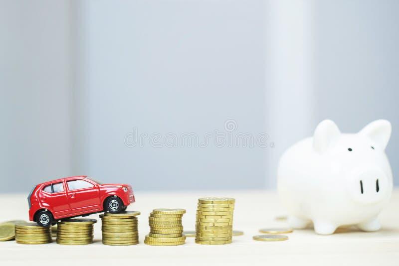 Weinig rode auto over heel wat geld stapelde muntstukken en spaarvarken royalty-vrije stock afbeelding
