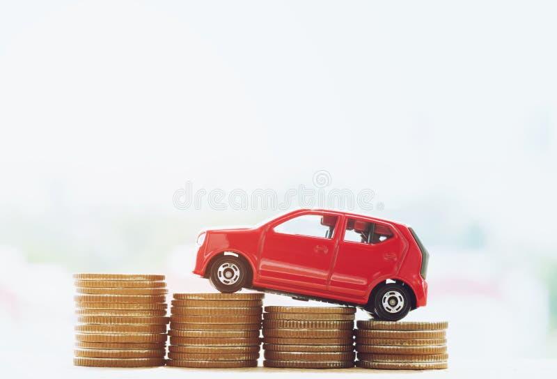 Weinig rode auto over heel wat geld stapelde muntstukken met achtergrondhuis stock foto's