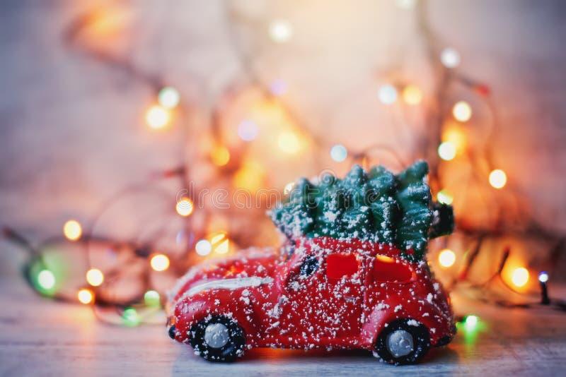 Weinig rode autostuk speelgoed dragende Kerstboom in sneeuw en bokeh Kerstmislichten stock foto's