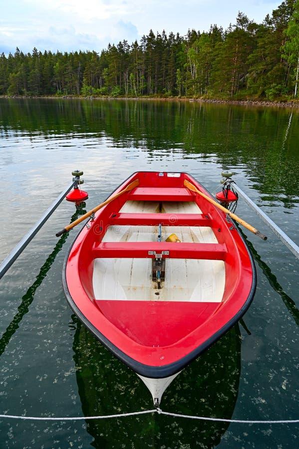 Weinig rode en witte skiff in Zweeds meer stock afbeelding