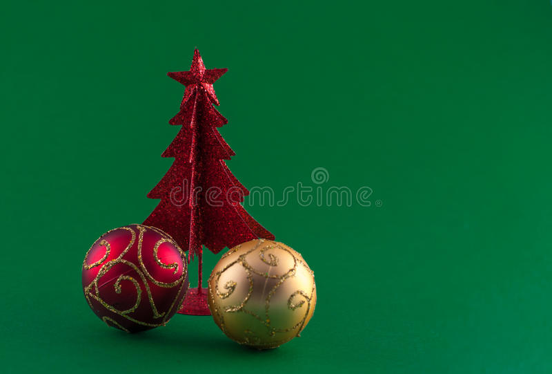 Weinig rode Kerstmisboom met boomversieringen op groene backgrou royalty-vrije stock afbeelding