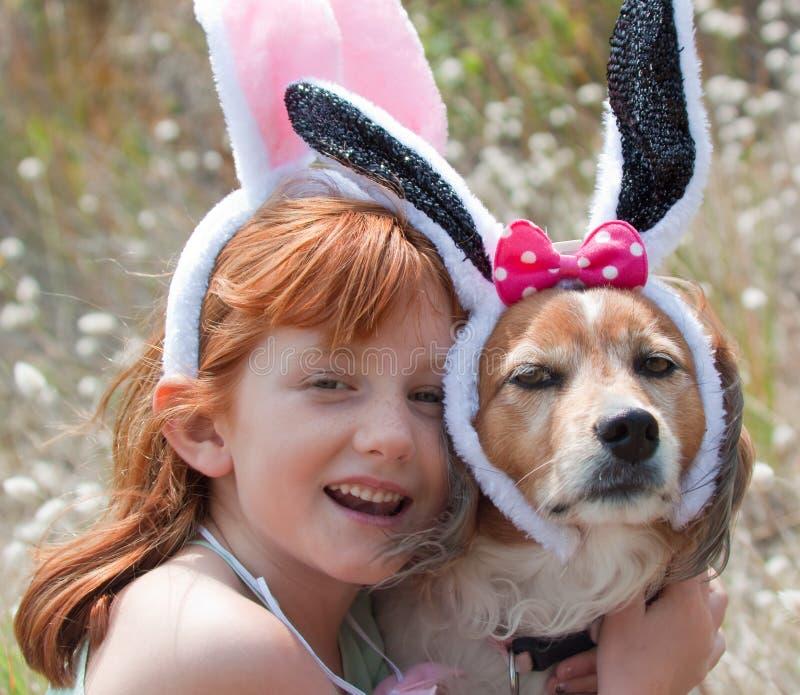 Weinig rood haired meisje met huisdierenhond kleedde zich omhoog in Pasen-konijntjesoren royalty-vrije stock afbeeldingen