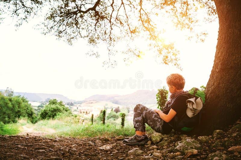Weinig rust van de backpackerreiziger onder boom bij de landweg stock afbeelding