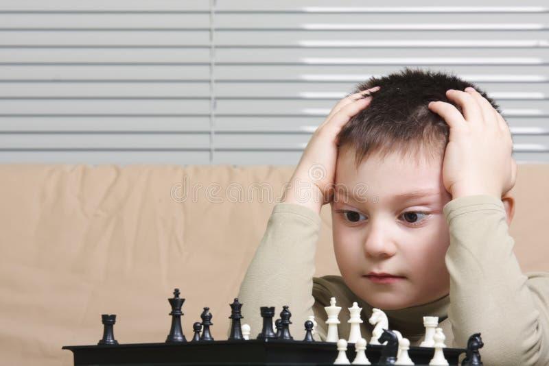 Weinig schaakspeler die hoofd omhelst stock afbeeldingen