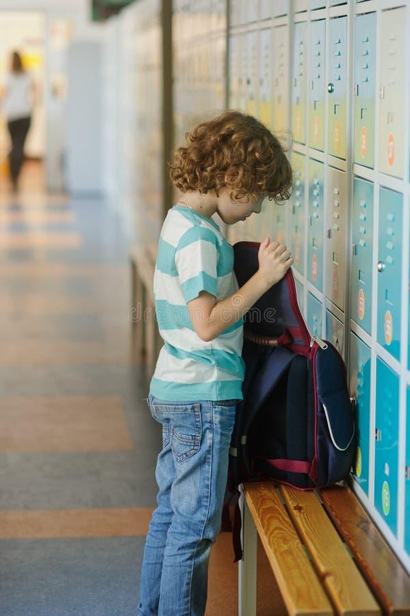 Weinig schooljongen die zich dichtbij kasten in schoolgang bevinden stock afbeeldingen