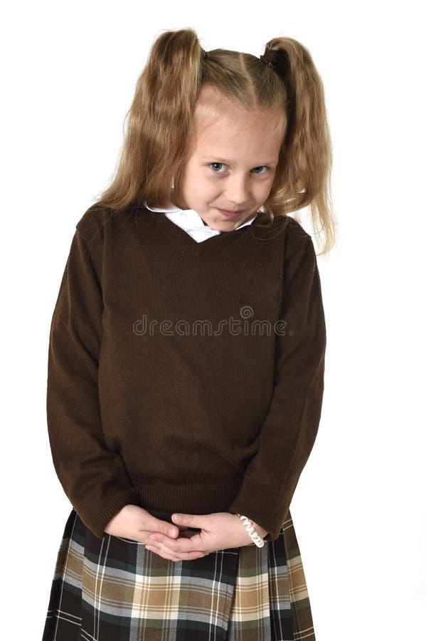 Weinig schoolmeisjemeisje met mooi blondehaar in school het eenvormige schuw en schuchter kijken royalty-vrije stock foto's
