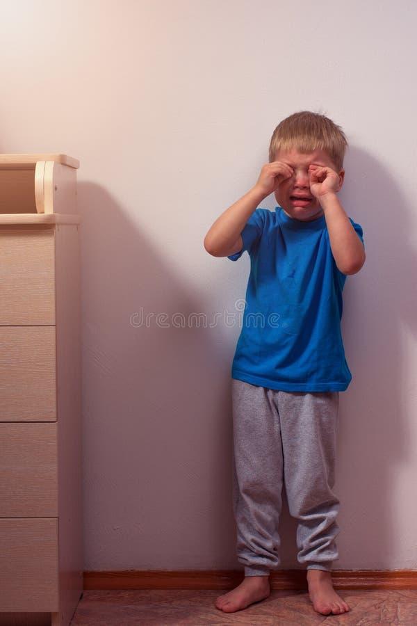 Weinig schreeuwende jongen die in hoek blijven Misbruikt kind stock afbeeldingen