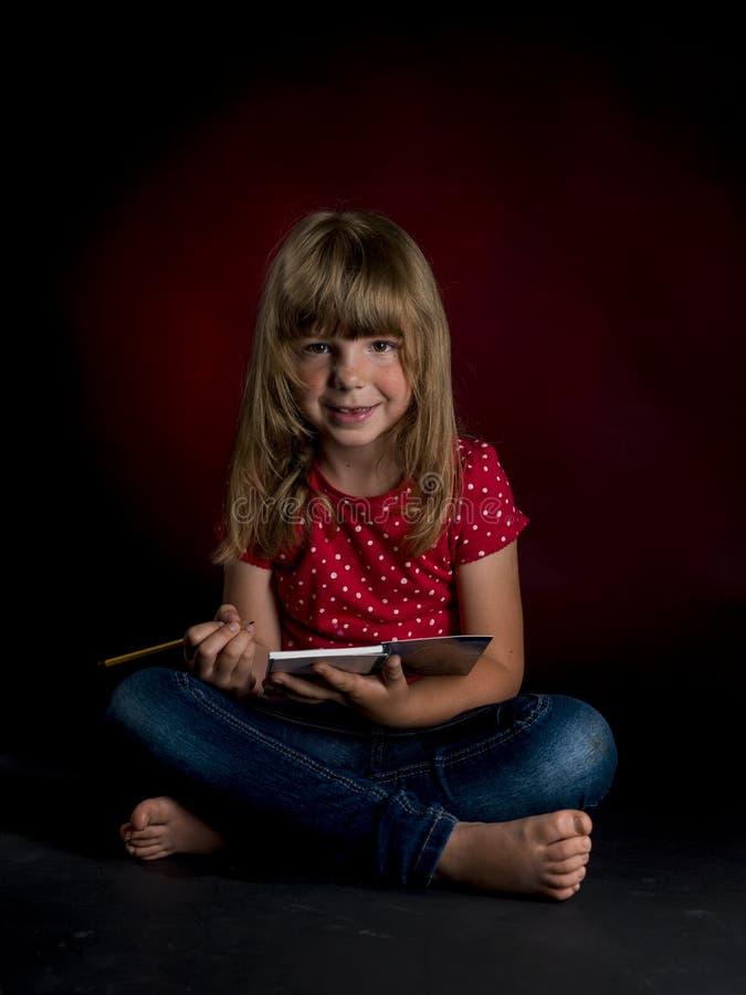 Weinig slordig meisje met potlood op de donkere achtergrond royalty-vrije stock foto's
