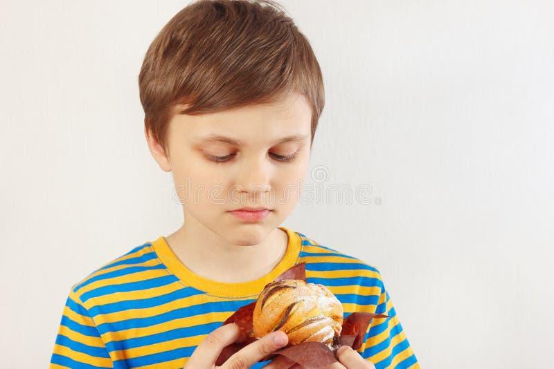 Weinig sneed jongen in een gestreept overhemd met appelcake op witte achtergrond royalty-vrije stock afbeelding