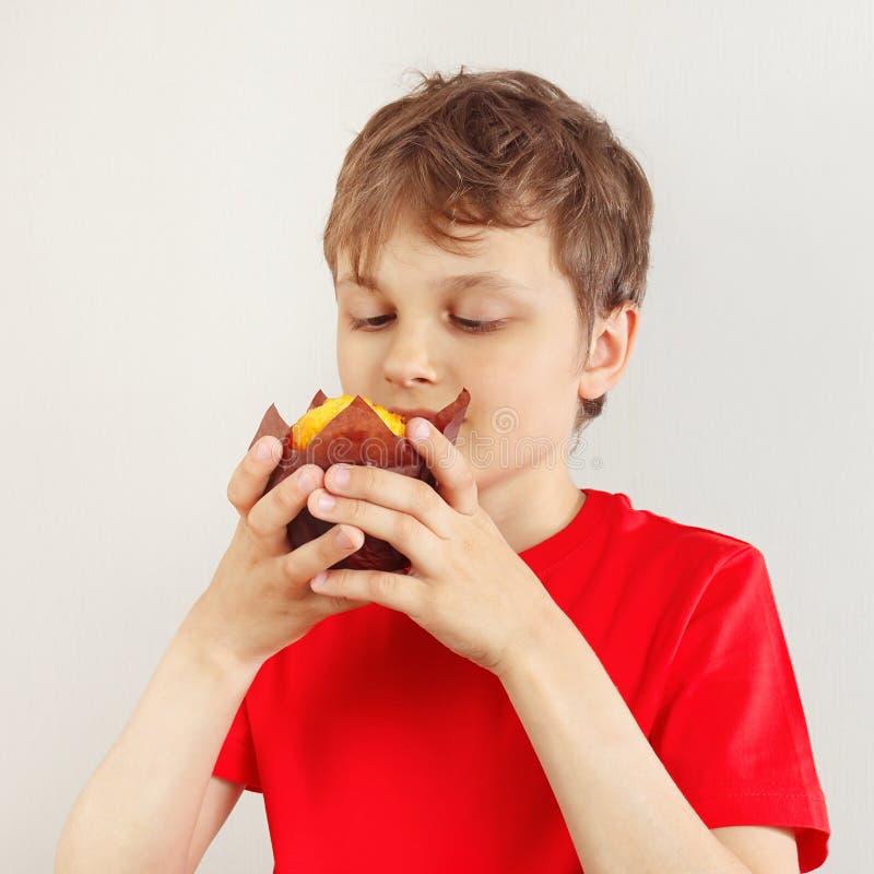 Weinig sneed jongen in een rood overhemd met muffin op witte achtergrond royalty-vrije stock afbeeldingen