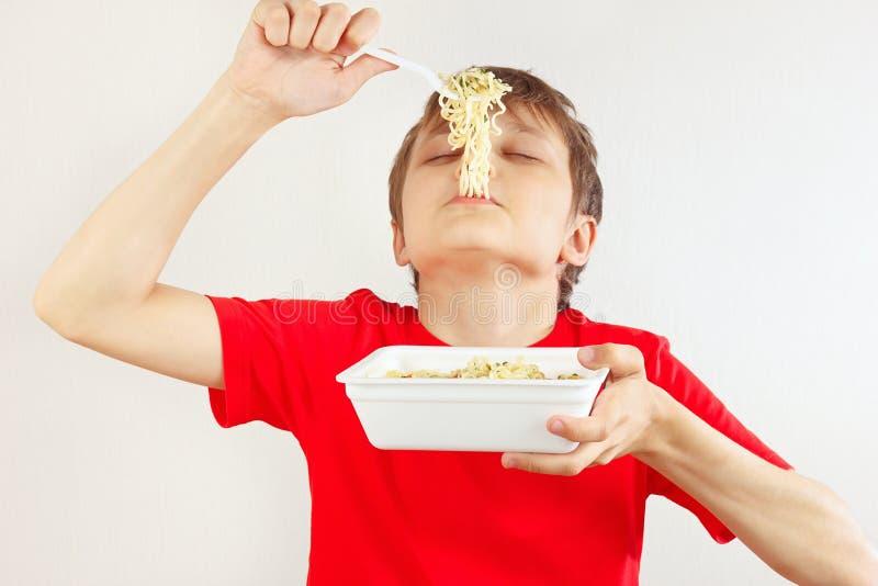 Weinig sneed jongen in een rood overhemd met onmiddellijke noedels op witte achtergrond stock foto
