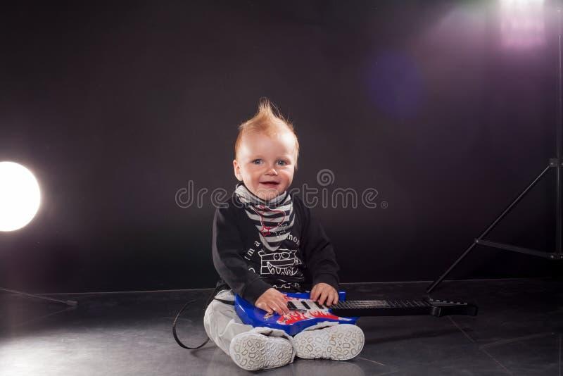 Weinig speelrock van de jongensmusicus op de gitaar stock foto's