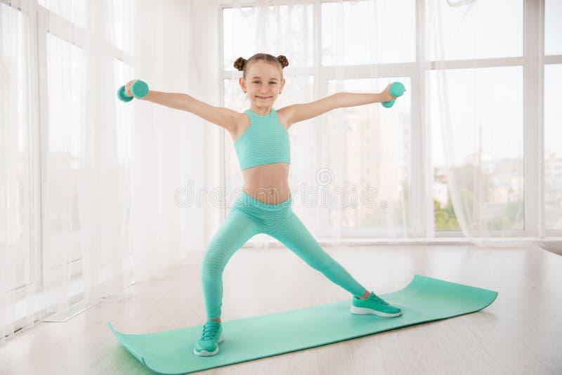 Weinig sportieve meisjesturner in sportkleding die oefeningen op een mat doen binnen stock fotografie