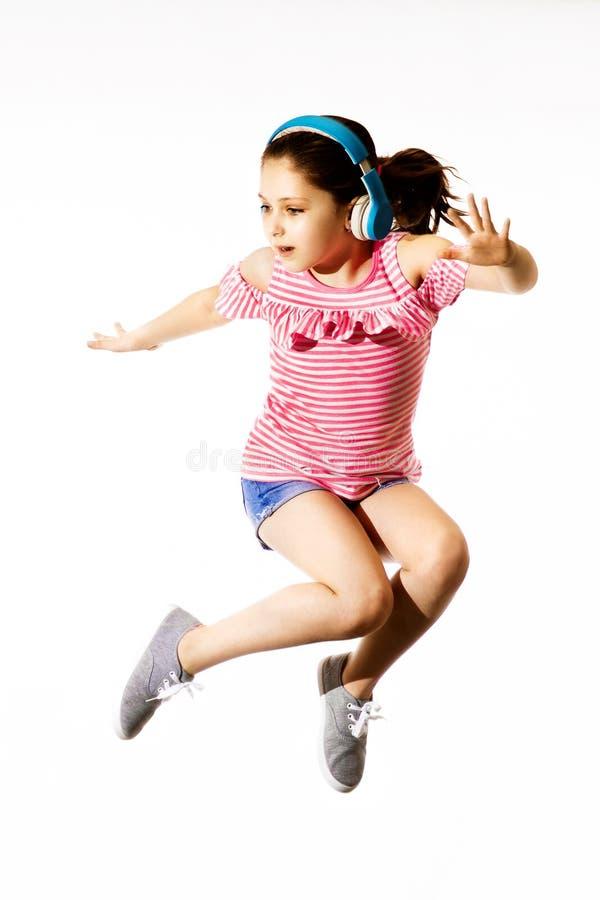 Weinig springend Kaukasisch meisje met hoofdtelefoons stock fotografie