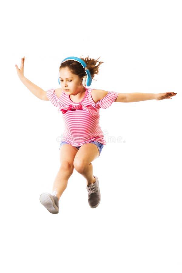 Weinig springend Kaukasisch meisje met hoofdtelefoons stock afbeelding