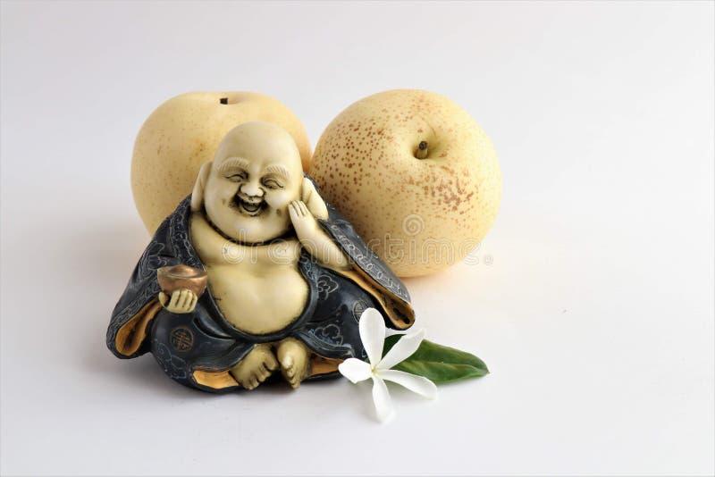 Weinig standbeeld van lachende Boedha met peren royalty-vrije stock afbeeldingen