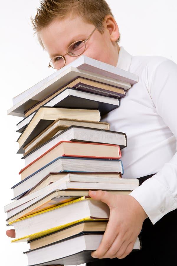 Weinig stapel van jongens dragende boeken stock fotografie
