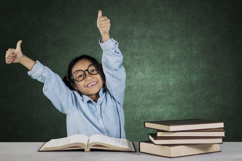 Weinig student die o.k. gebaar met boeken tonen stock afbeeldingen