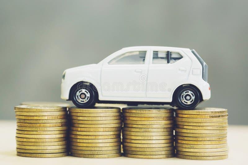 Weinig stuk speelgoed witte auto over heel wat geld stapelde muntstukken voor de financi verzekering, het kopen autofinanciën stock fotografie