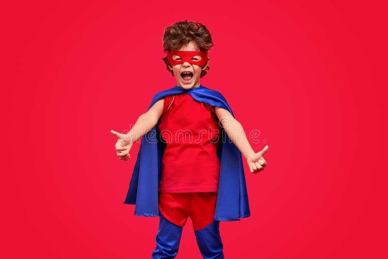 Weinig superhero het gesturing beduimelt omhoog royalty-vrije stock afbeelding