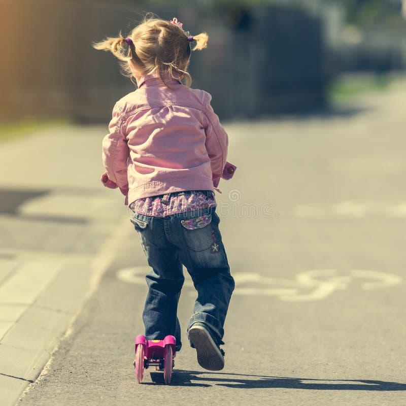 Weinig Twee jaar oud meisjes die haar autoped berijden royalty-vrije stock afbeelding