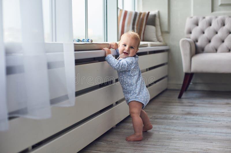 Weinig 8 van de babymaanden jongen bevindt zich thuis met steun dichtbij venster in witte ruimte stock afbeeldingen