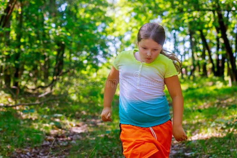 Weinig vrolijk meisje die, het spelen sporten in het park lopen royalty-vrije stock fotografie