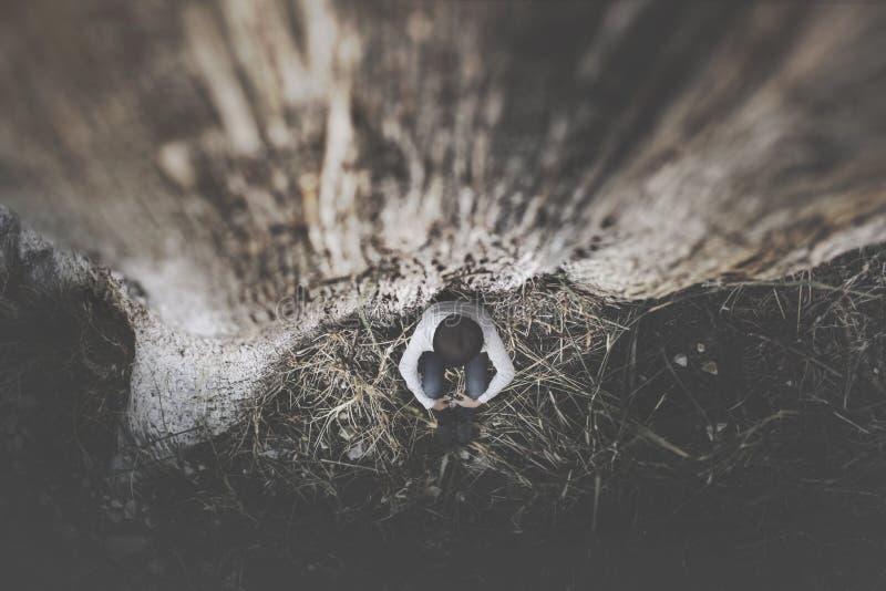 Weinig vrouw beschermt zich bang bij de voet van een reuzeboom in het hout stock foto