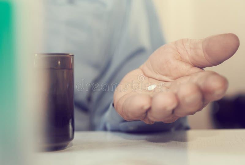 Weinig witte pil in de handen van een Oudste Pijnlijke oude dag Het geven voor de gezondheid van de bejaarden stock foto