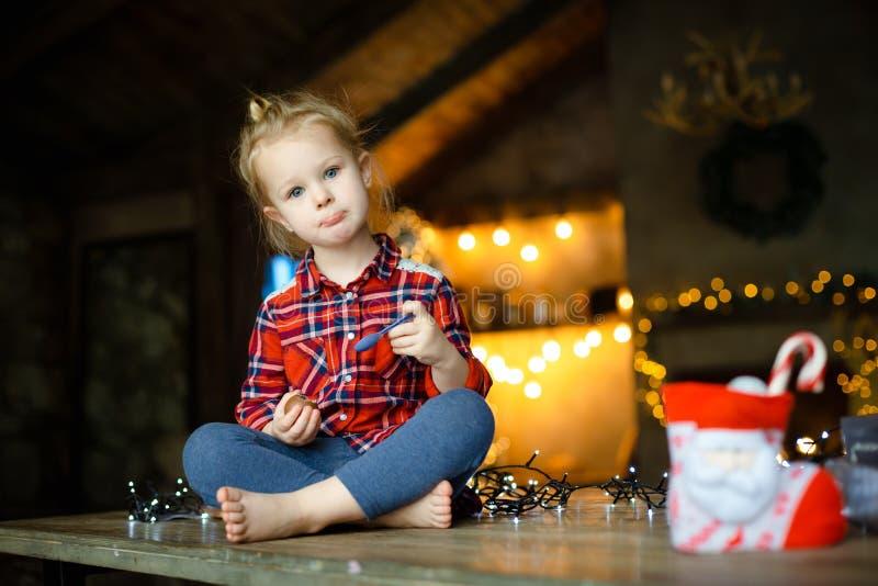 Weinig witte zitting van het blondemeisje op een houten die lijst in de woonkamer van het Chalet, voor Kerstboom wordt verfraaid  royalty-vrije stock foto