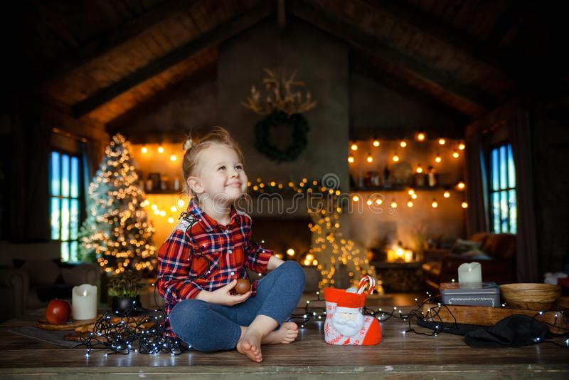 Weinig witte zitting van het blondemeisje op een houten die lijst in de woonkamer van het Chalet, voor Kerstboom wordt verfraaid  royalty-vrije stock fotografie