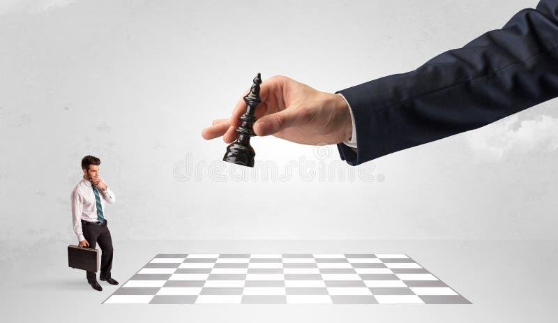 Weinig zakenman het spelen schaak met een groot handconcept stock afbeelding
