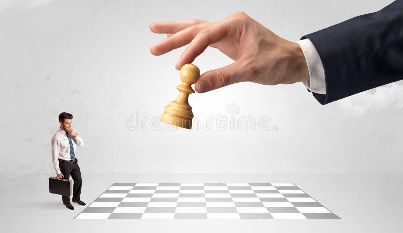 Weinig zakenman het spelen schaak met een groot handconcept royalty-vrije stock afbeelding