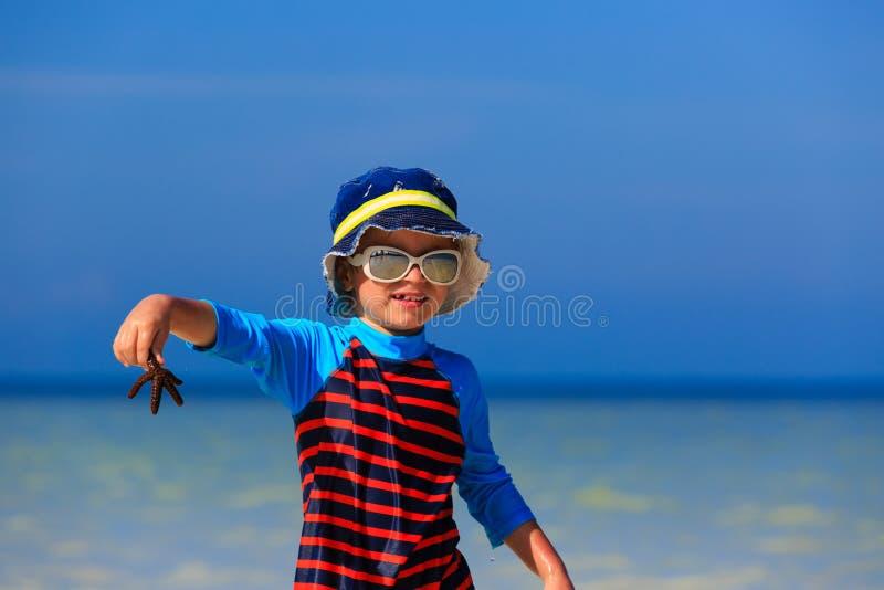Weinig zeester van de jongensholding bij de zomerstrand stock foto