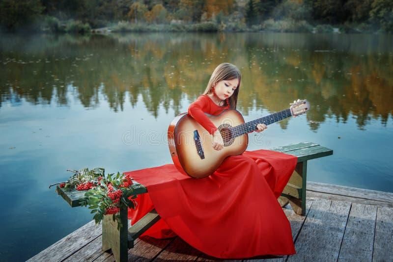 Weinig Zigeunermeisje in de rode kleding op de kust van het meer met een gitaar stock fotografie
