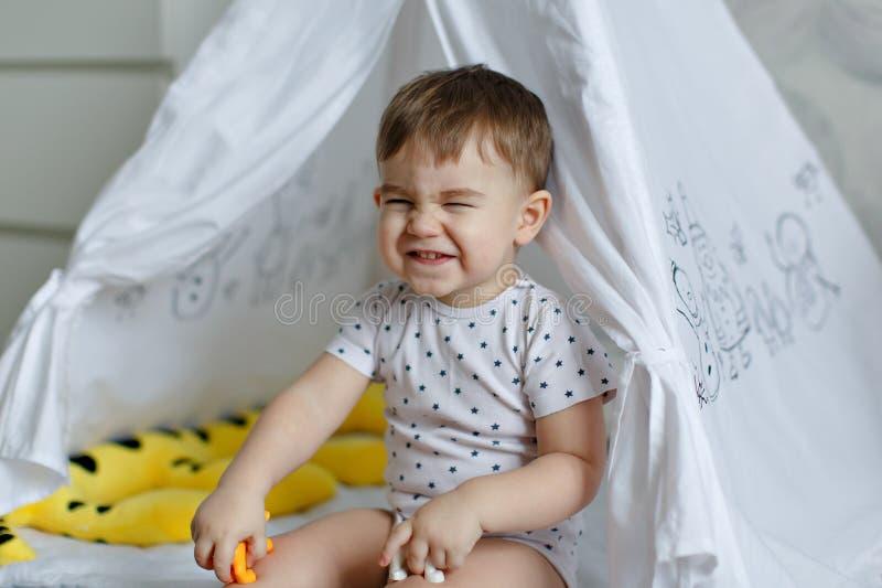 Weinig zitting van de babyjongen in een tipitent en grappige rimpels zijn n royalty-vrije stock foto's
