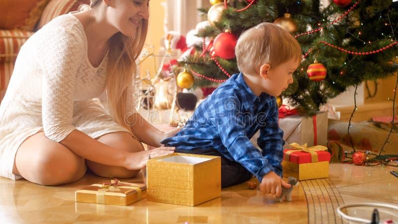Weinig zitting van de peuterjongen op vloer met mooie jonge moeder onder Kerstboom stock foto's