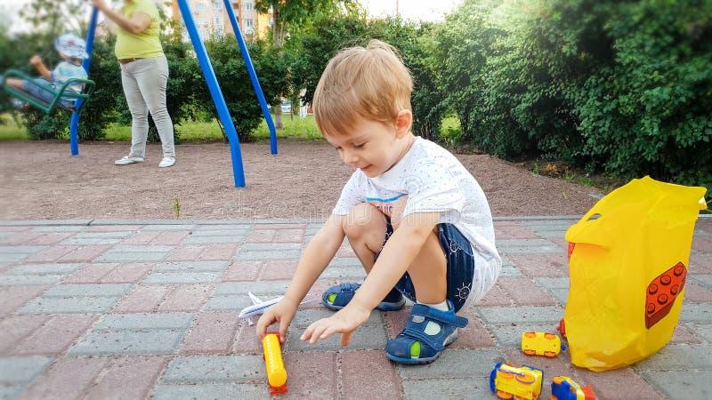 Weinig zitting van de peuterjongen ter plaatse bij park en het spelen met stuk speelgoed auto's stock foto's