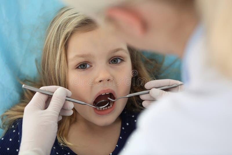 Weinig zitting van het babymeisje bij tandstoel met open mond en gevoel vrezen omhoog tijdens mondelinge controle terwijl arts vi stock afbeeldingen
