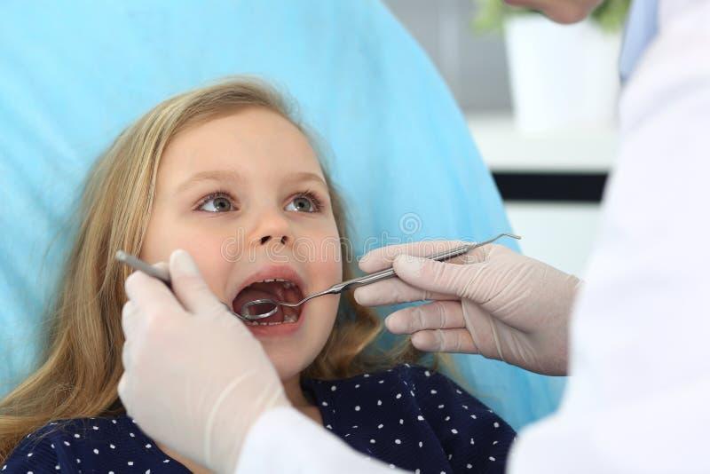 Weinig zitting van het babymeisje bij tandstoel met open mond en gevoel vrezen omhoog tijdens mondelinge controle terwijl arts vi royalty-vrije stock afbeeldingen