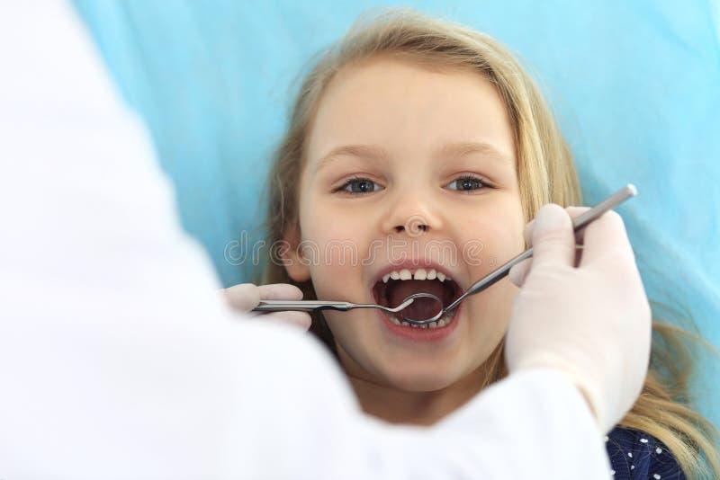 Weinig zitting van het babymeisje bij tandstoel met open mond tijdens mondelinge controle omhoog terwijl arts Bezoekend tandartsb stock foto's