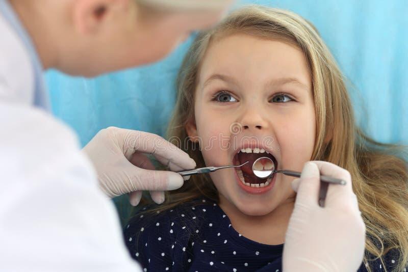 Weinig zitting van het babymeisje bij tandstoel met open mond tijdens mondelinge controle omhoog terwijl arts Bezoekend tandartsb royalty-vrije stock afbeeldingen