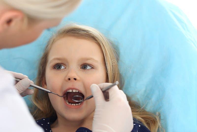 Weinig zitting van het babymeisje bij tandstoel met open mond tijdens mondelinge controle omhoog terwijl arts Bezoekend tandartsb stock afbeeldingen