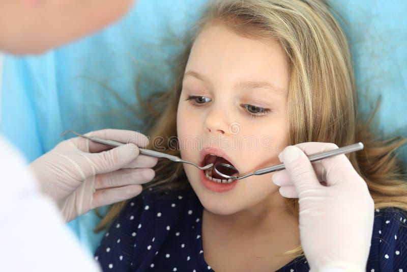 Weinig zitting van het babymeisje bij tandstoel met open mond tijdens mondelinge controle omhoog terwijl arts Bezoekend tandartsb royalty-vrije stock foto's
