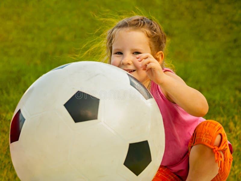 Weinig zitting van het babymeisje met een reusachtige bal van voetbalkleuren stock afbeelding