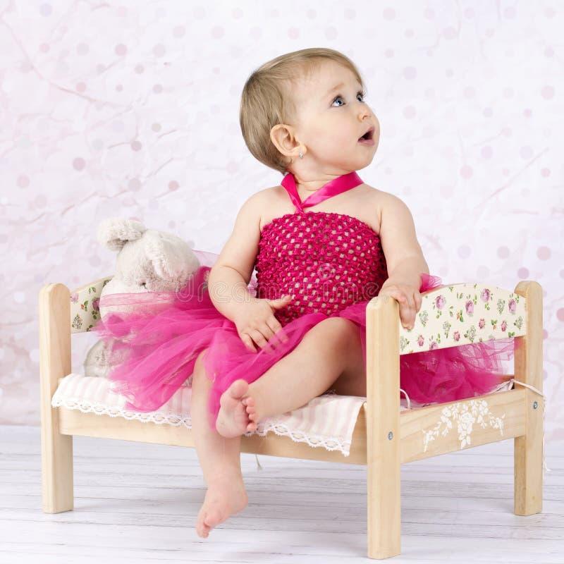 Weinig zitting van het babymeisje op het kleine bloemenbed royalty-vrije stock foto's