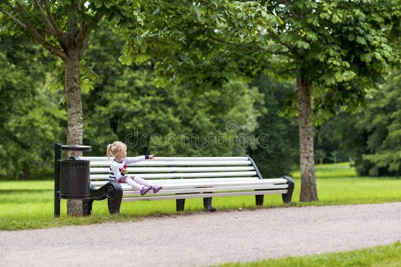 Weinig zitting van het blondemeisje op de bank in het park stock afbeeldingen