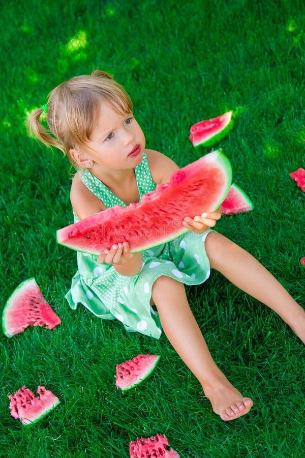 Weinig zitting van het blondemeisje op het gras rond plakken van watermeloen in de zomer ernstig stock fotografie