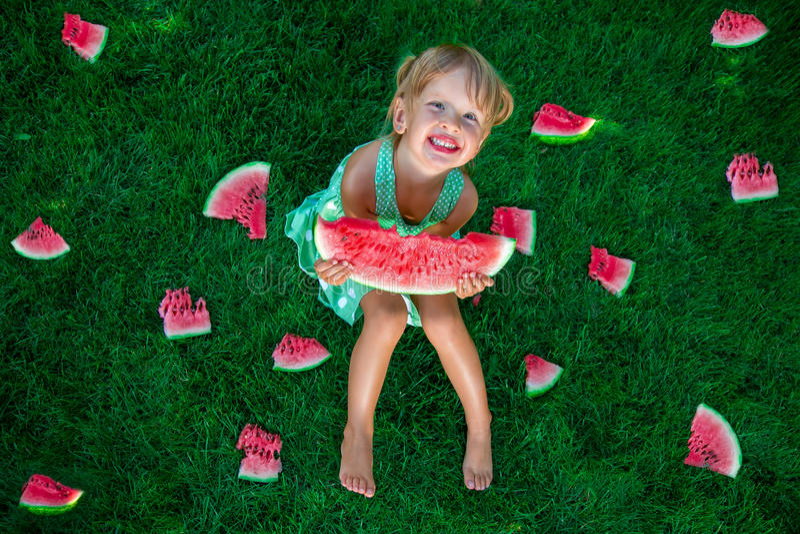 Weinig zitting van het blondemeisje op het gras rond plakken van watermeloen in de zomer gelukkig stock foto's