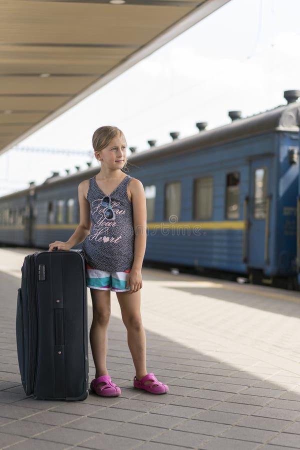 Weinig zoet meisje met een grote koffer op een verlaten spoorwegplatform meisje die een grote koffer op het platform trekken vert stock afbeeldingen